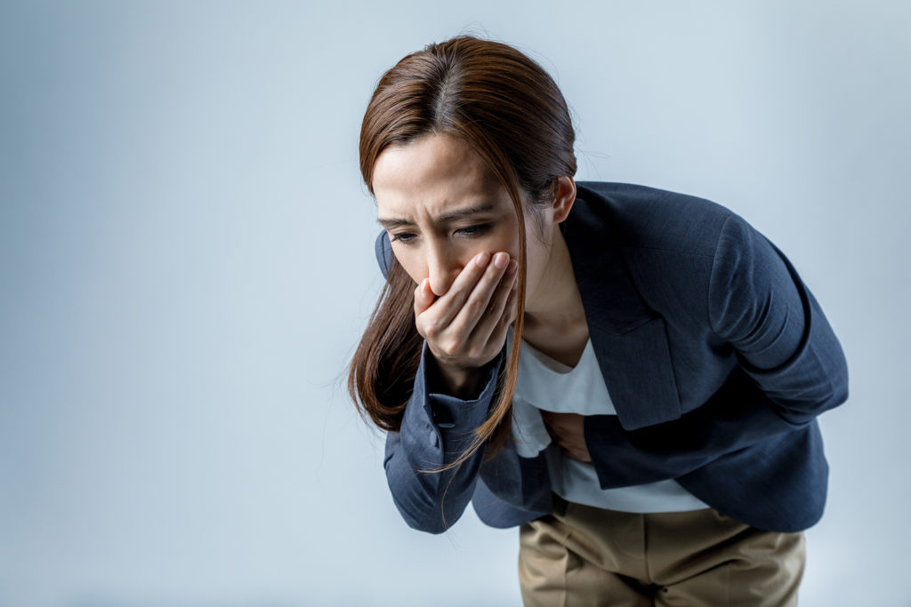 A woman 'pulling a whitey' and bending over as if ready to vomit. A white-out or to have 'whiteyed' can cause feelings of nausea, dizziness and weakness.