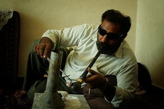 An Iranian man smokes opium using a traditional pipe; hashish is often mixed with opium in Iran - Sensi Seeds Blog