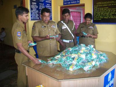 Sri Lankan police inspect confiscated package of madana modaka (© dinamina.lk)