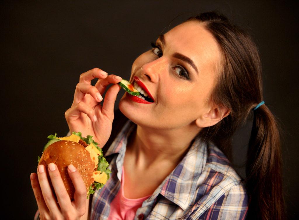 Woman with a hamburger eating.