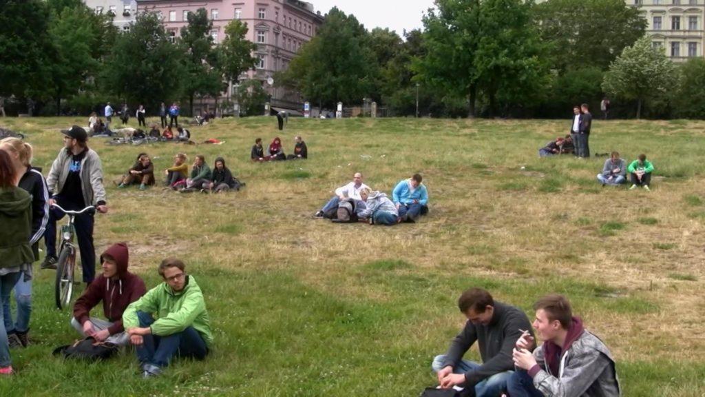 Fotografía del parque Görlitzer en Kreuzberg, Berlín. Hay pequeños grupos de personas sentados en el césped. Algunos parecen sostener lo que pueden ser porros.