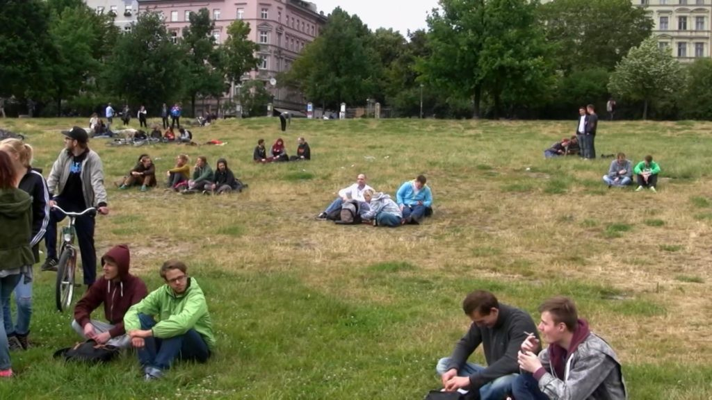 A photograph of Görlitzer Park in Kreuzberg, Berlin. Small groups of people sit on the grass. Some seem to be holding what may be joints.