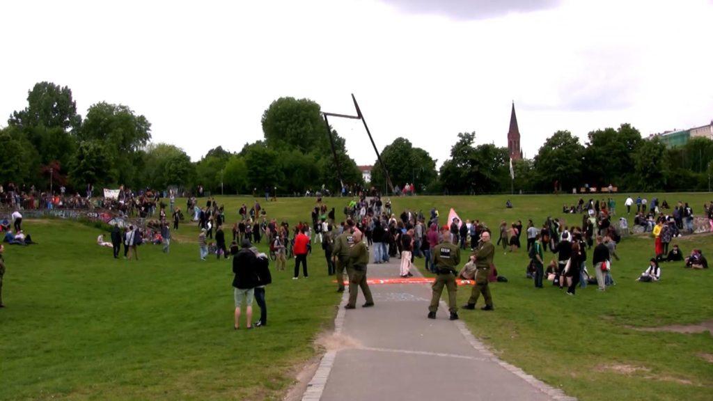 Fotografía del parque Görlitzer en Kreuzberg, Berlín. Hay un gran grupo de personas reunidas a lo lejos. Algunos parecen sostener pancartas. Parece ser una protesta.