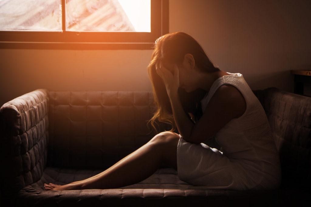Een vrouw zit in de lengte op een bank met haar ellebogen op haar dijen en haar hoofd in haar handen. De kamer is donker, afgezien van een klein zonnestraaltje dat door het raam schijnt. De vrouw lijkt depressief.