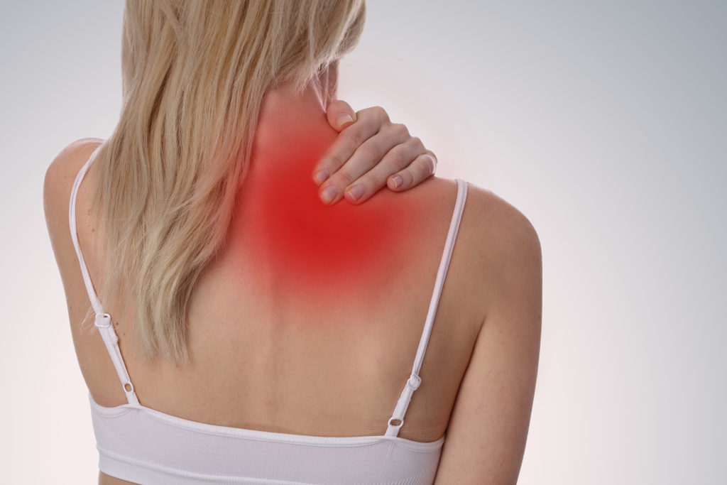 Die Fotografie des Rückens einer Frau. Ihr linker Arm ruht auf ihrer rechten Schulter und umgekehrt. Die rötliche Färbung um den oberen Rücken und die Schultern deuten Muskelspasmen an.
