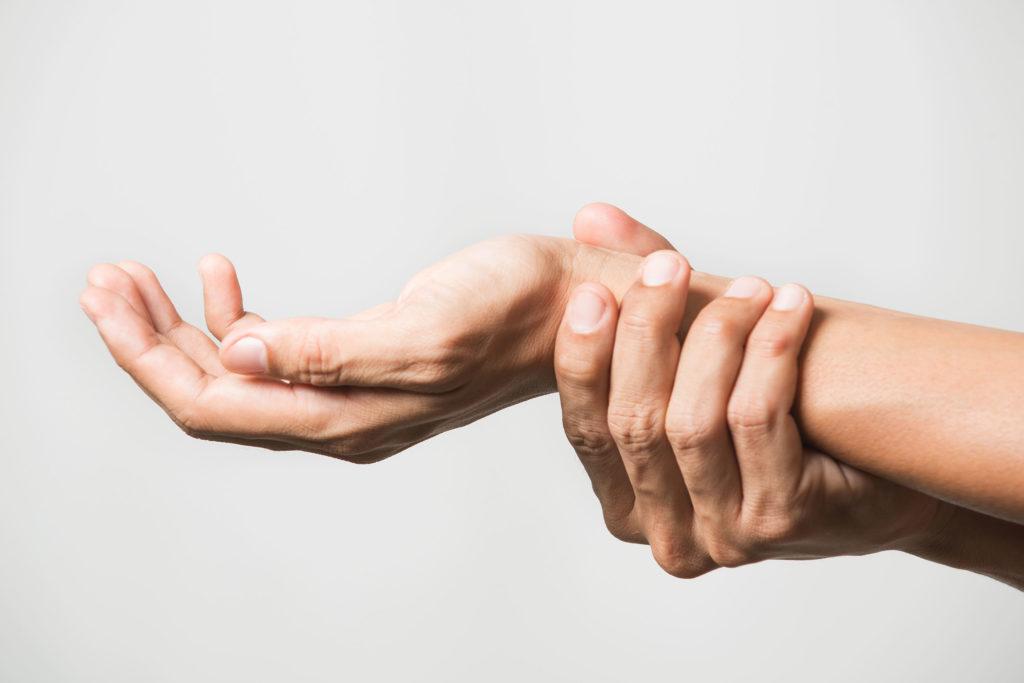 Nahaufnahme eines Handgelenkes, das von der anderen Hand umfasst wird.