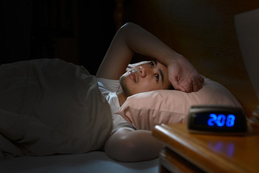 Fotografía que muestra a un hombre acostado despierto en la cama. Tiene el brazo derecho sobre la frente. Tiene los ojos abiertos. El reloj de la mesita de noche dice que son las 2:08. Está oscuro en la habitación.