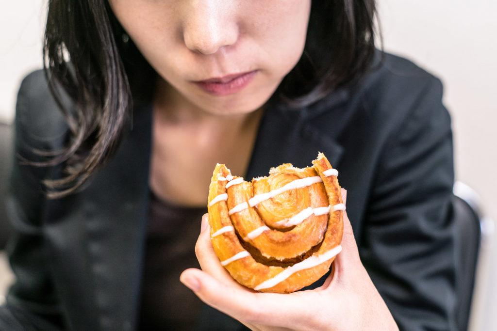 Photo prise à distance moyenne d'une femme, du nez jusqu'au torse, elle tient une pâtisserie de laquelle a été prise une grosse bouchée. Elle mâche la nourriture.