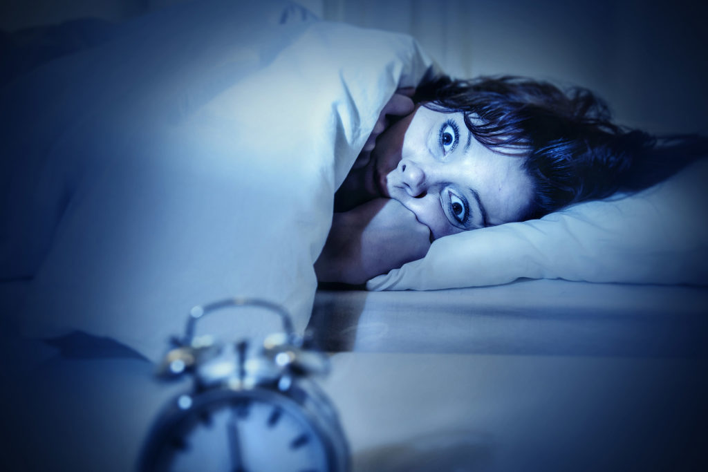 A photograph of a woman who lies awake at night in her bed with her eyes wide open. Her hands in at her face. An alarm clock is in the foreground of the image.