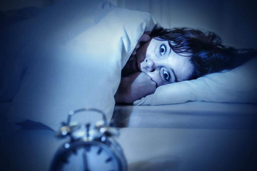 Een foto van een vrouw die 's nachts met wijd open ogen wakker ligt in haar bed. Ze heeft haar handen in haar gezicht. Op de voorgrond van de afbeelding staat een wekker.