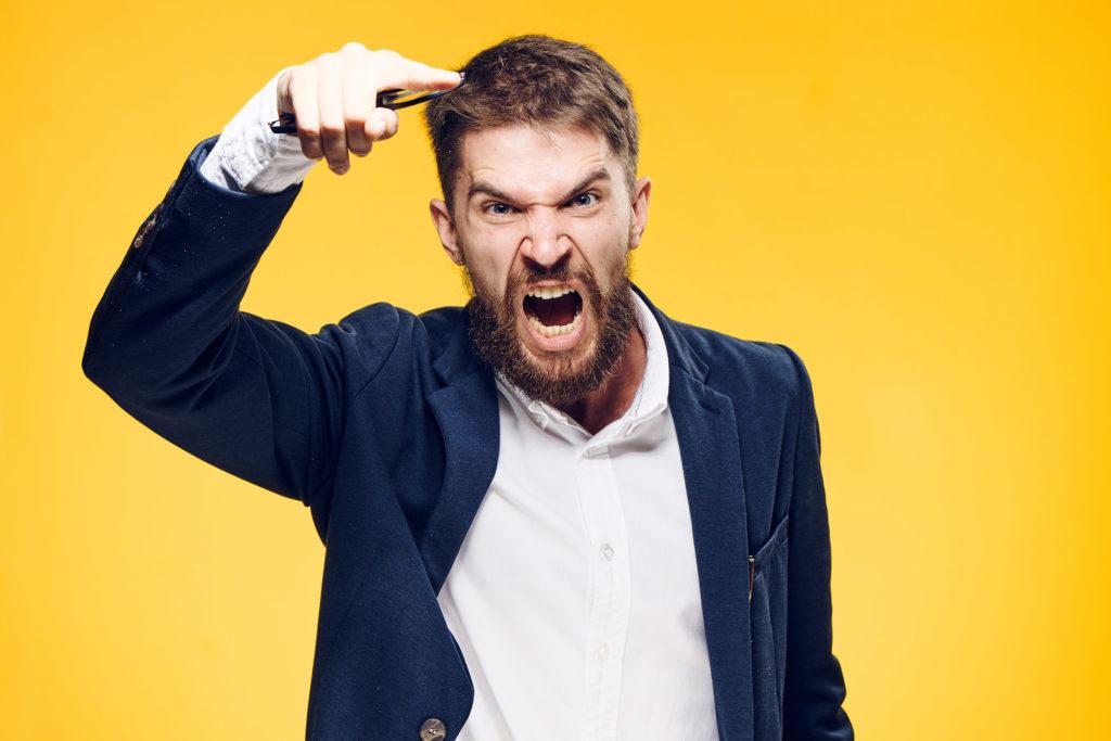 Un hombre enojado con barba se encuentra delante de un fondo de color naranja brillante y grita a la cámara. Tiene el brazo derecho levantado y apuntando.