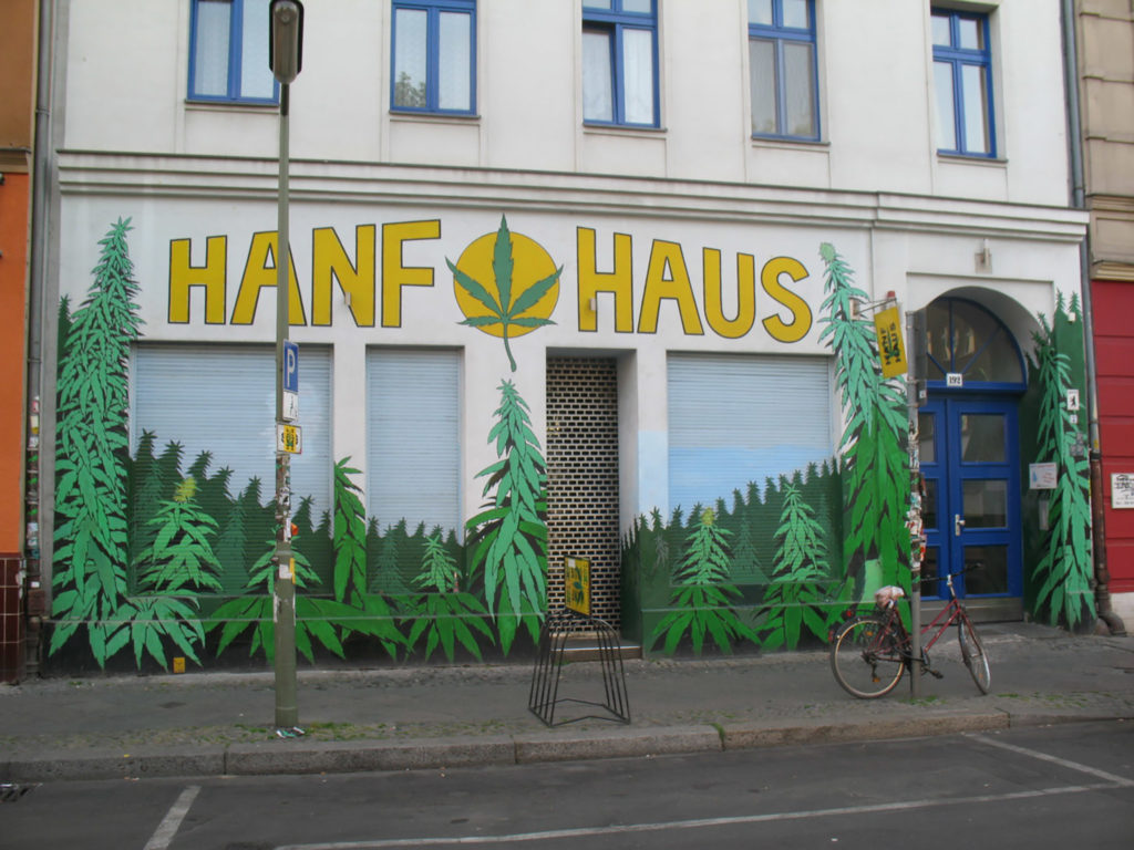 A photograph of a hemp shop, in Switzerland, Kreuzberg. The facade of the building reads Hanf Haus and is surrounded by painted depictions of marijuana leaves.