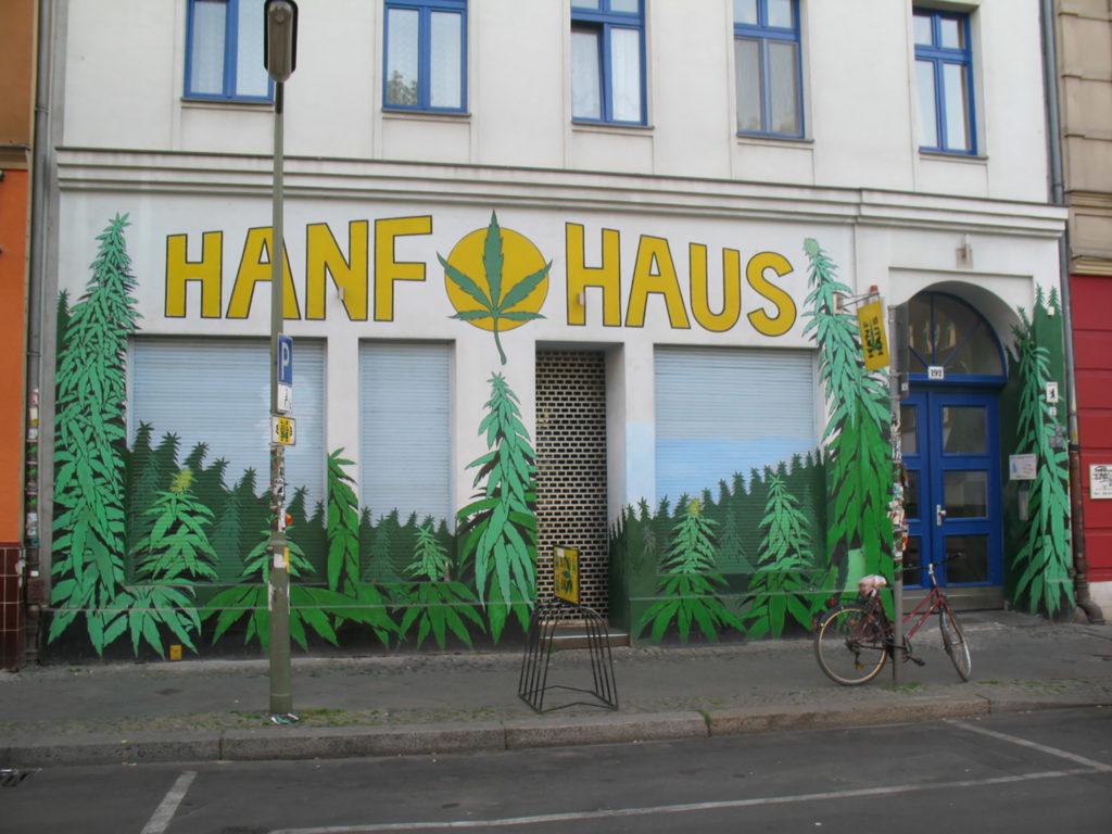 Een foto van een hennepwinkel in Kreuzberg, Zwitserland. Op de voorgevel van het gebouw staat 'Hanf Haus', omringd door geschilderde afbeeldingen van marihuanabladeren.