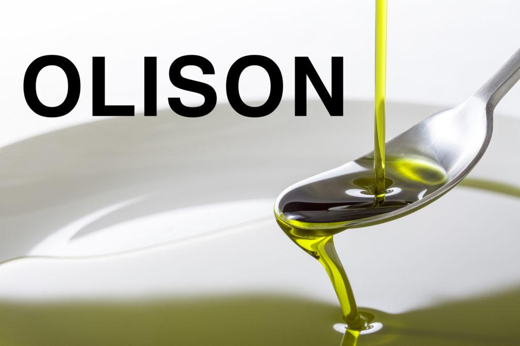 Fotografía de una cucharilla de metal en la que cae aceite verde translúcido, que se derrama de la cuchara formando un charco de más aceite. Las palabras OLISON están escritas en mayúsculas grandes en la parte superior izquierda de la imagen.