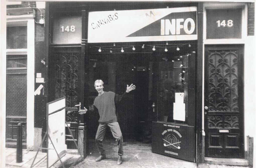 Un joven alan frente al museo de información de cáñamo con los brazos extendidos
