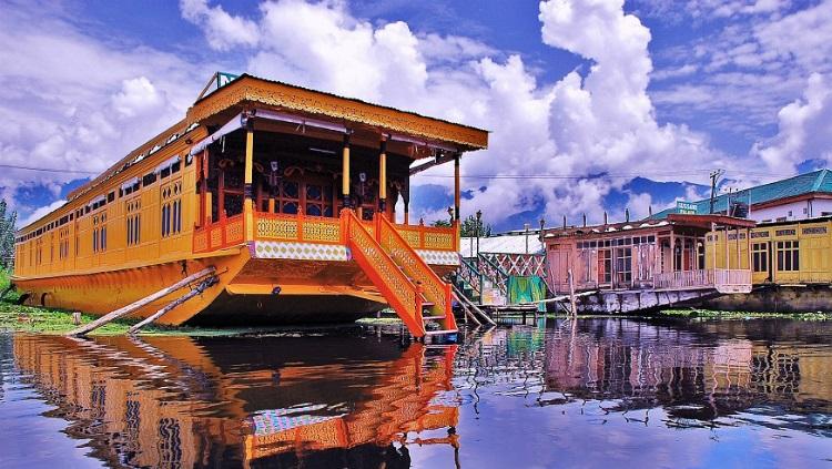 Una casa flotante naranja en el lago Dal en Cachemira sobre un fondo de montañas