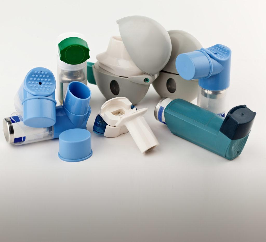 Een foto van een groep verschillende soorten inhalators met salbutamol. In de astmatische longen is te zien dat de bronchiën van de longen ontstoken zijn, zodat de luchtstroom wordt beperkt en geblokkeerd.