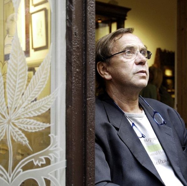 Ben Dronkers con una chaqueta y gafas grises, apoyado contra una puerta marrón