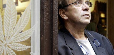 Ben dronkers dragen een grijze jas en een bril, leunend tegen een bruine deuropening