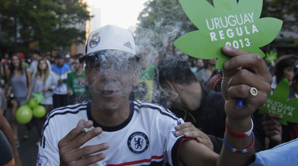 """A photograph of young man at a busy protest wearing sports clothing. He exhales smoke, while holding a joint in his right hand, and a cut-out of a marijuana leaf in his left. On the leaf are the words """"Uruguay Regula 2013""""."""