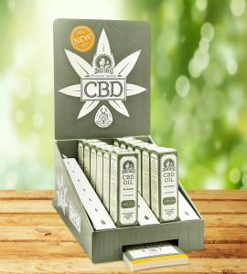 Fotografía de un embalaje POS para aceite de CBD de Sensi Seeds, sobre una mesa de madera y con un segundo plano desenfocado. En ella podemos ver doce embalajes individuales de aceite de CBD. Debajo del embalaje POS hay un montón de cartulinas del tamaño de tarjetas de visita.