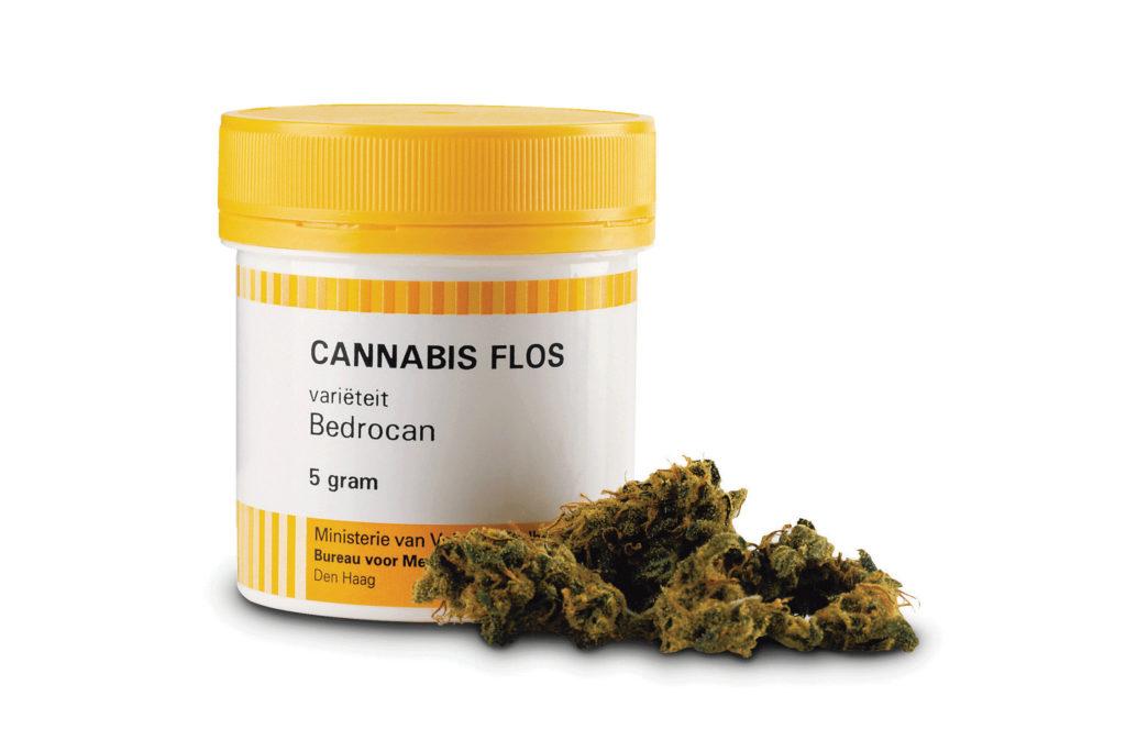 """Op de foto staat de geel met witte verpakking van medicinale cannabis met de naam """"Cannabis Flos"""". Er zit 5 g van de Bedrocan-soort in. Voor de verpakking staan cannabisbloemen."""