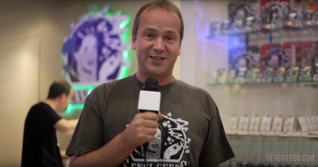 Un homme dans une t-shirt Sensi Germes tenant un microphone dans une boutique de graines de sensi