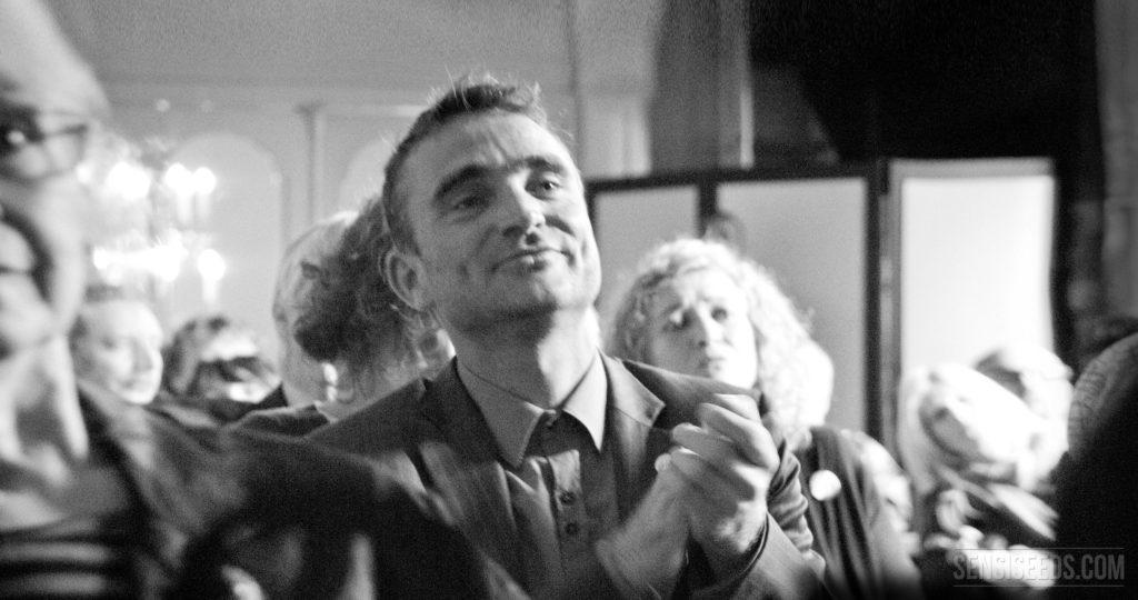 Een zwart-witte foto van een man klappen. Hij is in een menigte mensen