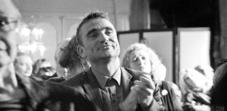 Eine schwarze und weiße Fotografie eines Mannes klatschen. Er ist in einer menge von menschen