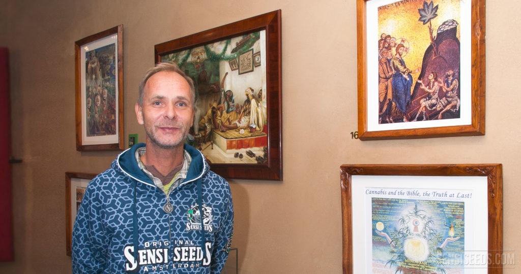 Alan Dronkers con una sudadera con capucha de Sensi Semillas de pie contra una pared cubierta en pinturas enmarcadas