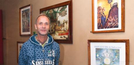 Alan Dronkers trägt einen Sensi-Samen-Hoodie, der an einer mit gerahmten Gemälden bedeckten Wand steht