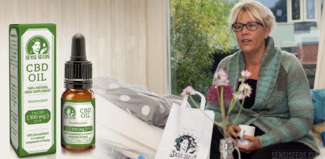 Fotomontage waarop links de verpakking en fles van de CBD-olie van Sensi Seeds te zien is, en rechts de patiënte Thea Hali die op een ziekenhuisbed zit en een theebeker vasthoudt. Op een tafel voor haar staat een papieren zak van Sensi Seeds en een vaas met bloemen. Op de achtergrond zijn door een raam de contouren van een woonhuis en een boom zichtbaar.