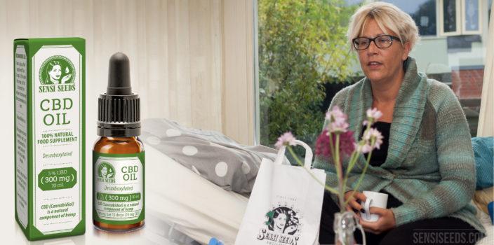 Fotomontaje donde vemos a la izquierda el envase y el frasco del aceite de CBD de Sensi Seeds y a la derecha a la paciente Thea Hali, sentada en una cama de hospital y sosteniendo una taza de té. En una mesa delante de ella hay una bolsa de papel de Sensi Seeds y un jarrón con flores. En un segundo plano vemos a través de una ventana los contornos de una vivienda y un árbol.