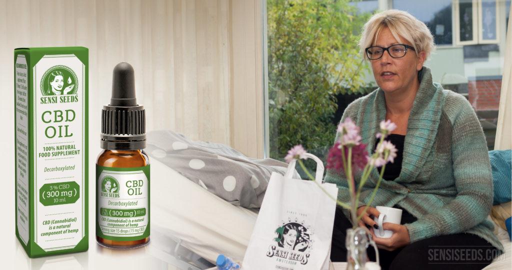 Photomontage avec, à gauche, la boîte et le flacon d'huile au CBD de Sensi Seeds et à droite, la patiente Thea Hali assise sur un lit médicalisé, un mug à la main. Sur une table devant elle, on voit un sac en papier Sensi Seeds et un vase avec des fleurs. À l'arrière-plan, on aperçoit une maison avec un jardin à travers une fenêtre.