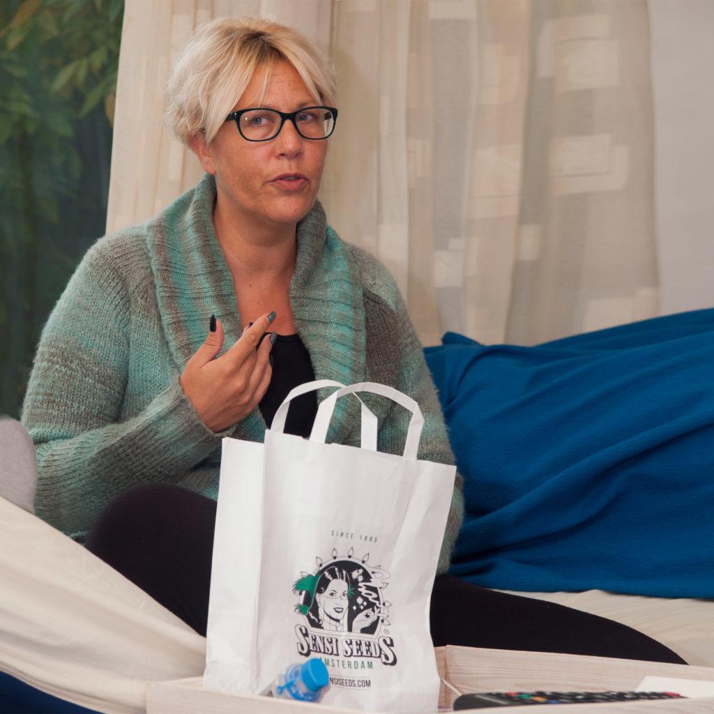 Fotografía de Thea Hali sentada en una cama de hospital, haciendo un gesto explicativo con la mano derecha. Delante de ella hay una bolsa de papel de Sensi Seeds. Thea lleva gafas y un jersey de lana y tiene las uñas pintadas de oscuro.