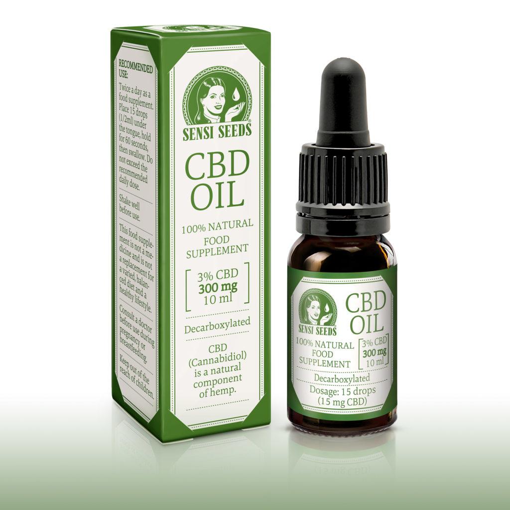 Productfoto van CBD-olie van Sensi Seeds, links de verpakking, rechts de fles. In een grote letters is CBD-olie te zien en daarnaast Sensi Seeds-logo. De kleurstelling is doorgaans wit en groen. Links op de verpakking staan de dosering en de aanbevolen toepassing aangegeven, op de voorkant zien we dat het gaat om een 100% natuurlijk, gedecarboxyleerd voedingssupplement van 10 ml. Het gemiddelde CBD-gehalte bedraagt 3%, totaal 300 mg. Dezelfde informatie staat ook op de fles.