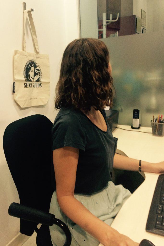 Fotografía de la paciente Covadonga F., tomada desde un lateral, sentada en un escritorio en una oficina. Detrás de ella hay una bolsa de Sensi Seeds colgando de un gancho.