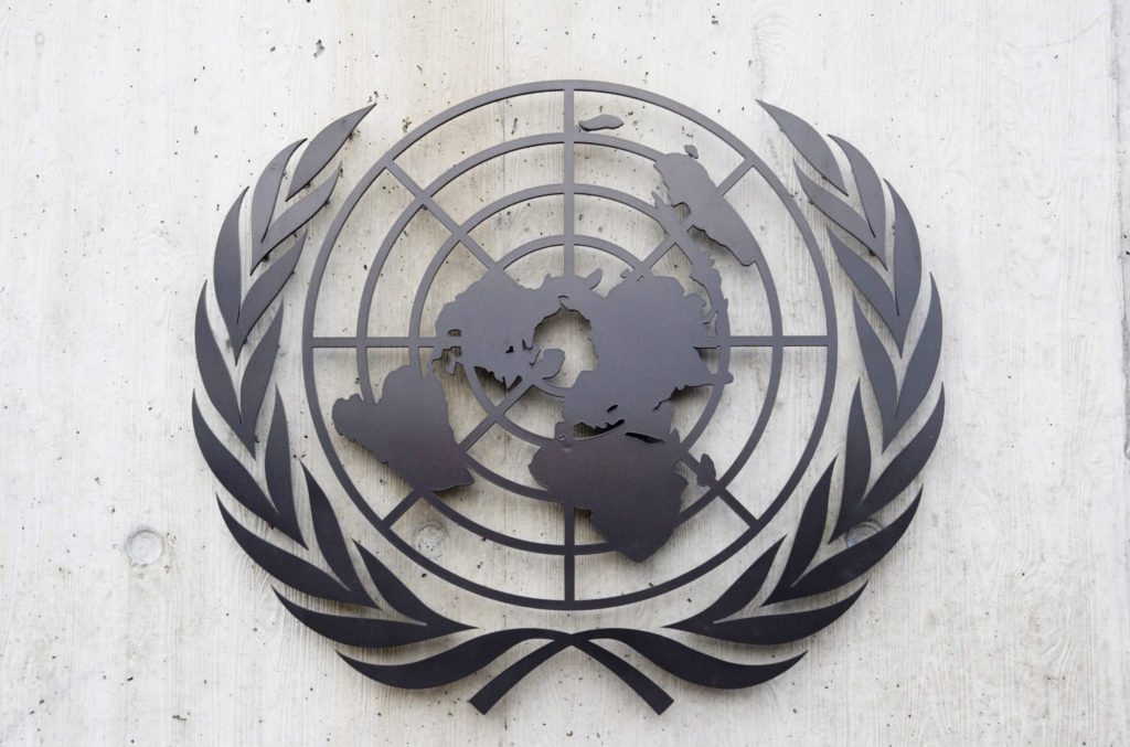 A photo of the emblem of the United Nations (a world map with olive branches on either side), made of metal and attached to a wall