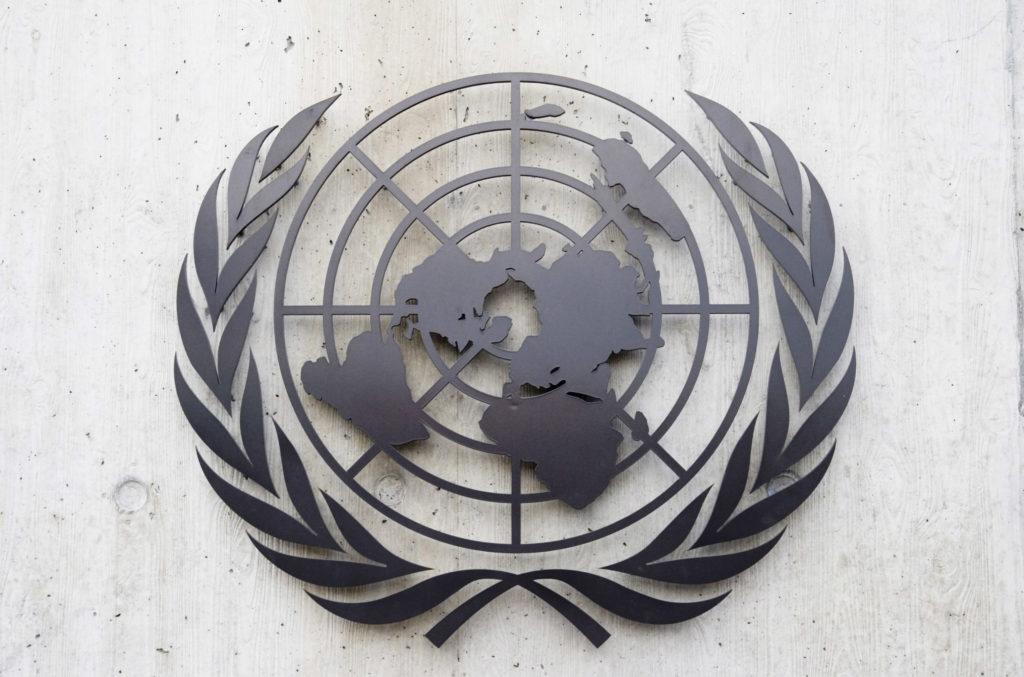 Een foto van het embleem van de Verenigde Naties (een wereldkaart met olijftakken aan weerszijden), gemaakt van metaal en bevestigd aan een muur