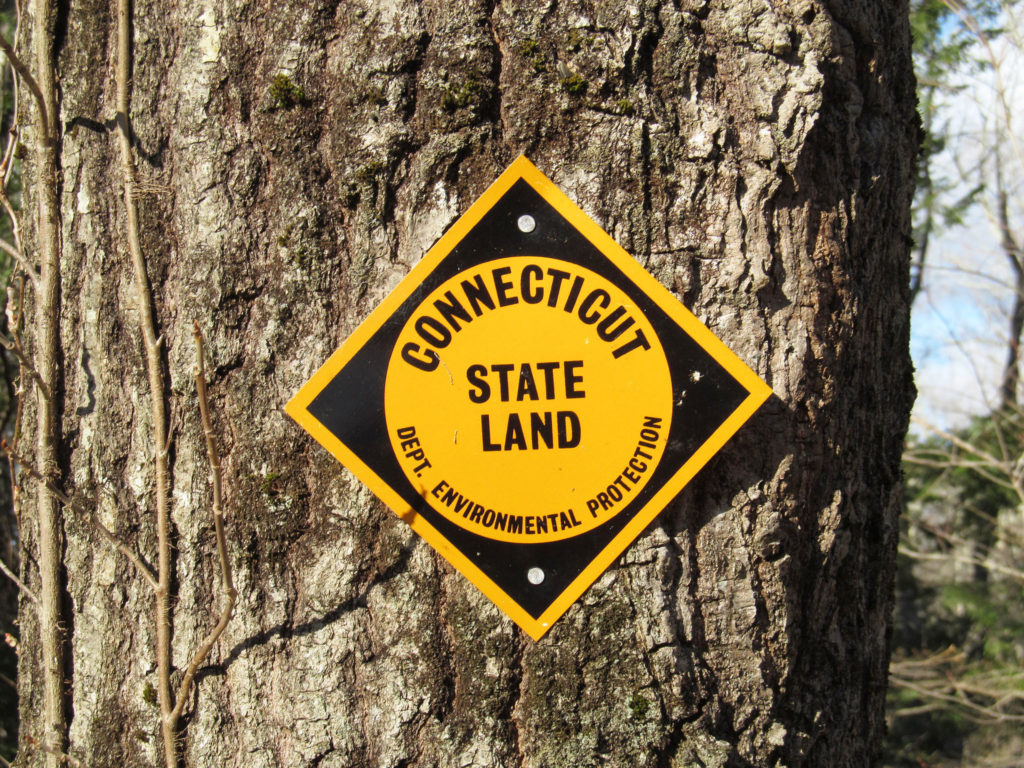 A photograph of a yellow and black sign that reads Connecticut State Land Dept. Environmental Protection
