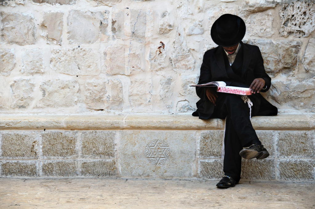 A photograph of a rabbi sitting on a wall reading the Tanakh, the Hebrew Bible