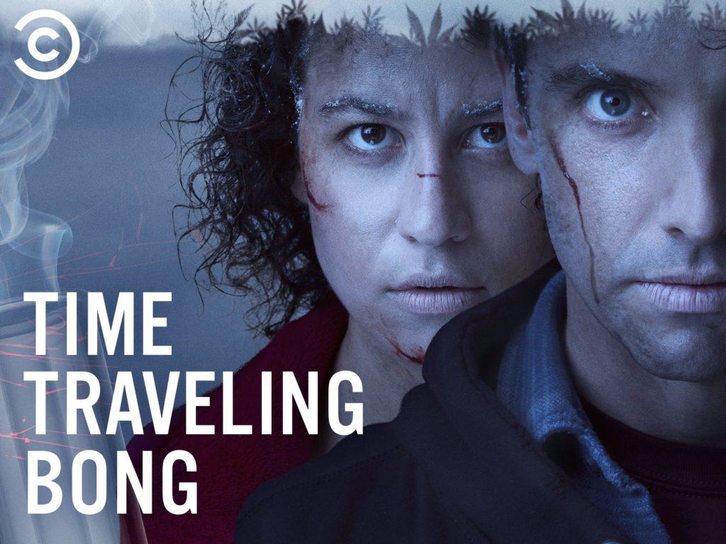 Een close-up van de gezichten van de acteurs Ilana Glazer en Paul W. Downs in hun rollen Sharee en Jeff uit de serie Time Traveling Bong. Ze hebben beiden kleine sneetjes in hun gezicht en sneeuw op hun wenkbrauwen. In de linkerbenedenhoek staat 'Time Traveling Bong'.