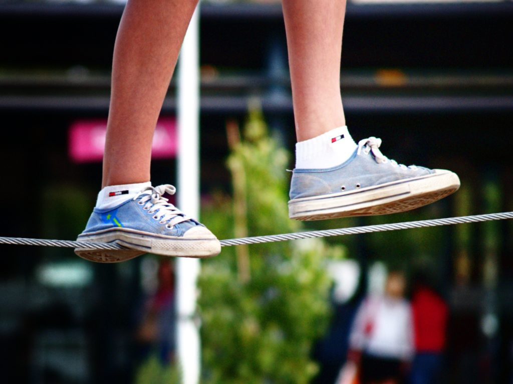 A photograph of two feet in trainers balancing on a tightrope