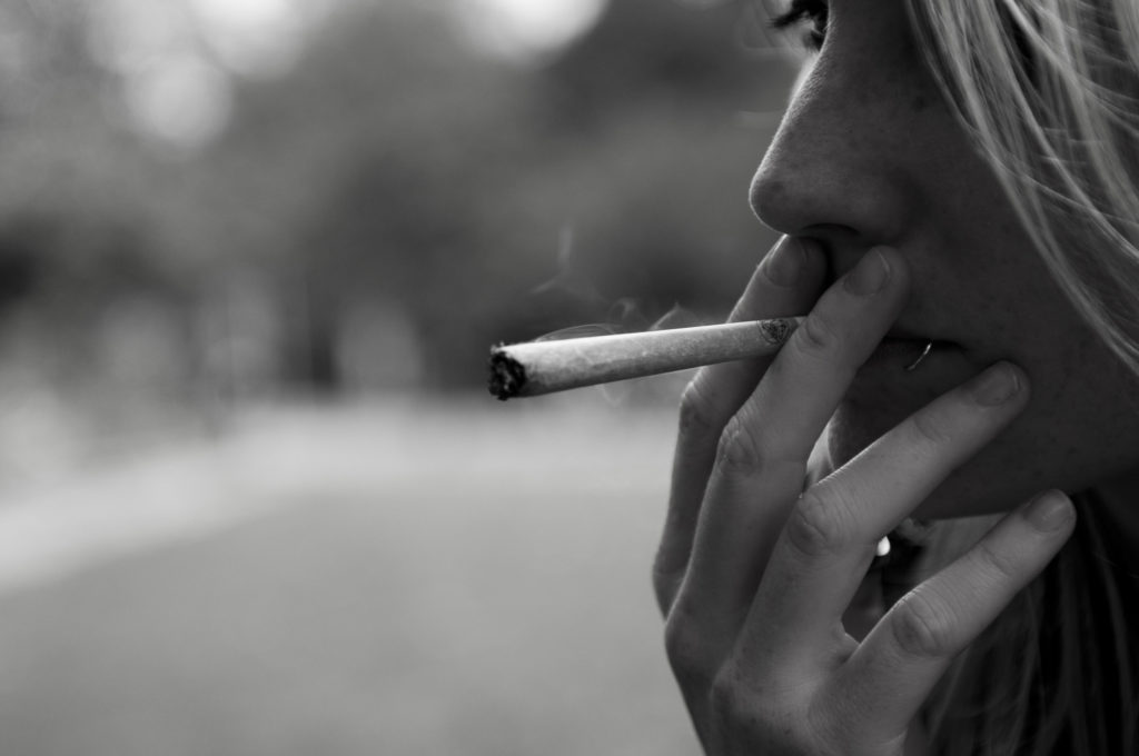 A black and white close-up photograph of a person smoking a joint