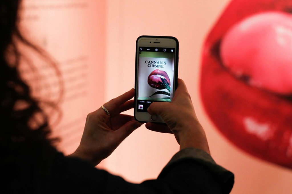 Een foto van het silhouet van links van een persoon met lang, krullend haar, de handen met een telefoon geheven naar het midden van het beeld. De persoon neemt een foto van een muur rechts. Hieromheen is een vrouwenmond met fel rode lippenstift afgebeeld.
