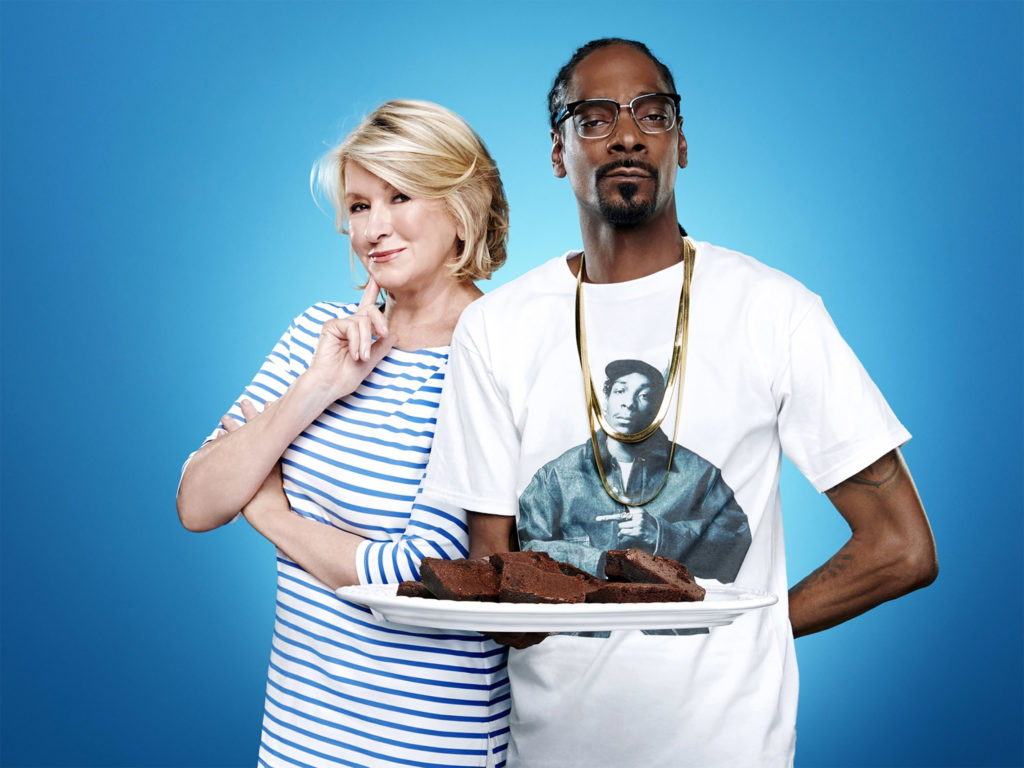 Photo de Martha Stewart et de Snoop Dogg au centre, ce dernier tenant une grande assiette contenant des space brownies, sur fond bleu.