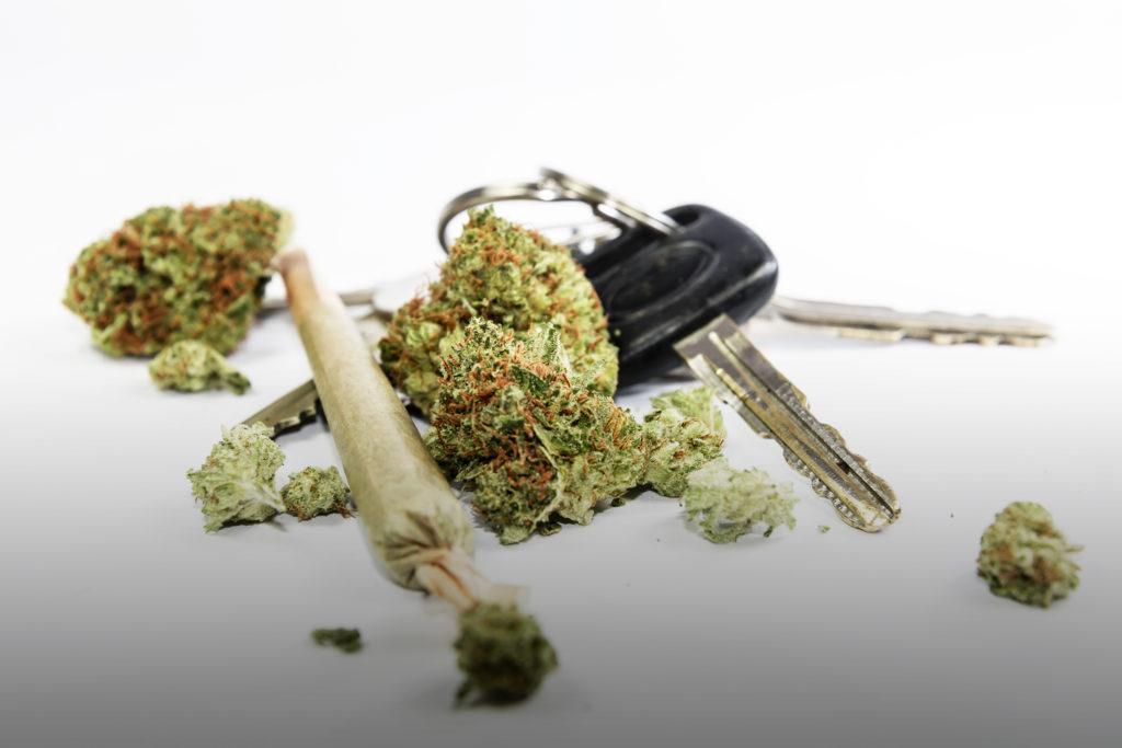 Primer plano de un porro de cannabis, unos cogollos de cannabis podados y recortados, y las llaves de un coche sobre un fondo blanco.