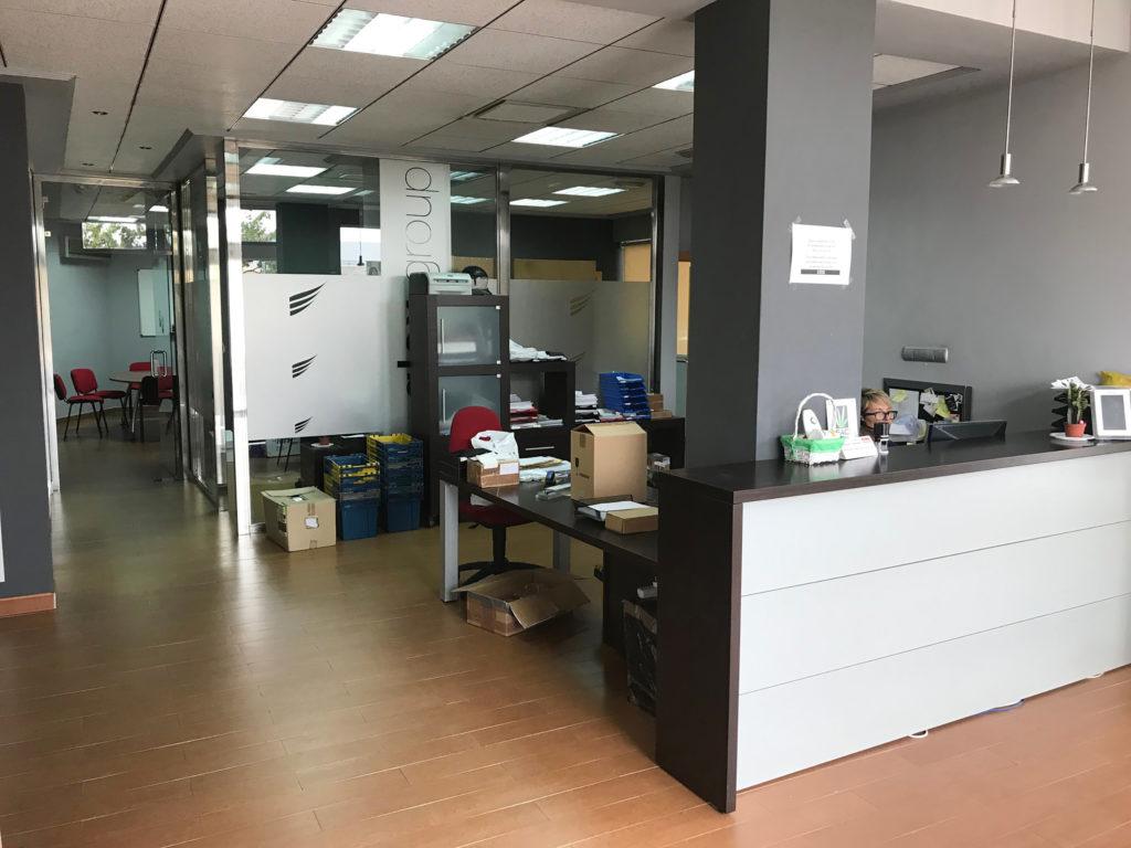 Een foto van het kantoor van LaMarihuana.com. Een vrouw met bril zit achter een bureau. De muren zijn grijs en de houten vloer bruin. In de ruimte liggen her en der bezorgdozen.