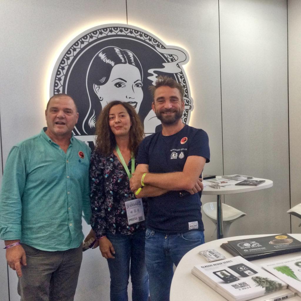 Miranda en Ravi Spaarenberg van Sensi Seeds samen met Jesús Mac van LaMarihuana.com bij de stand van Sensi Seeds op Spannabis Madrid 2017. Achter hen is een groot Sensi Seeds-logo. Voor hen staat een ronde, witte tafel met folders, flyers en stickers van Sensi Seeds.