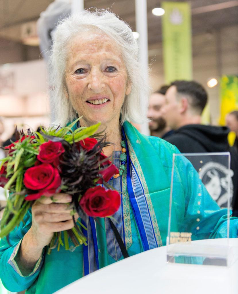 Ein Foto der Cannabis-Ikone Michka. Sie hält einen Blumenstrauß und trägt eine blaugrüne Jacke. Vor ihr steht ein Glaspreis auf einem Tisch. Sie ist auf dem Cannafest 2017. Hinter ihr ist ein Mann zu sehen, der einen Hoodie von Sensi Seeds trägt.